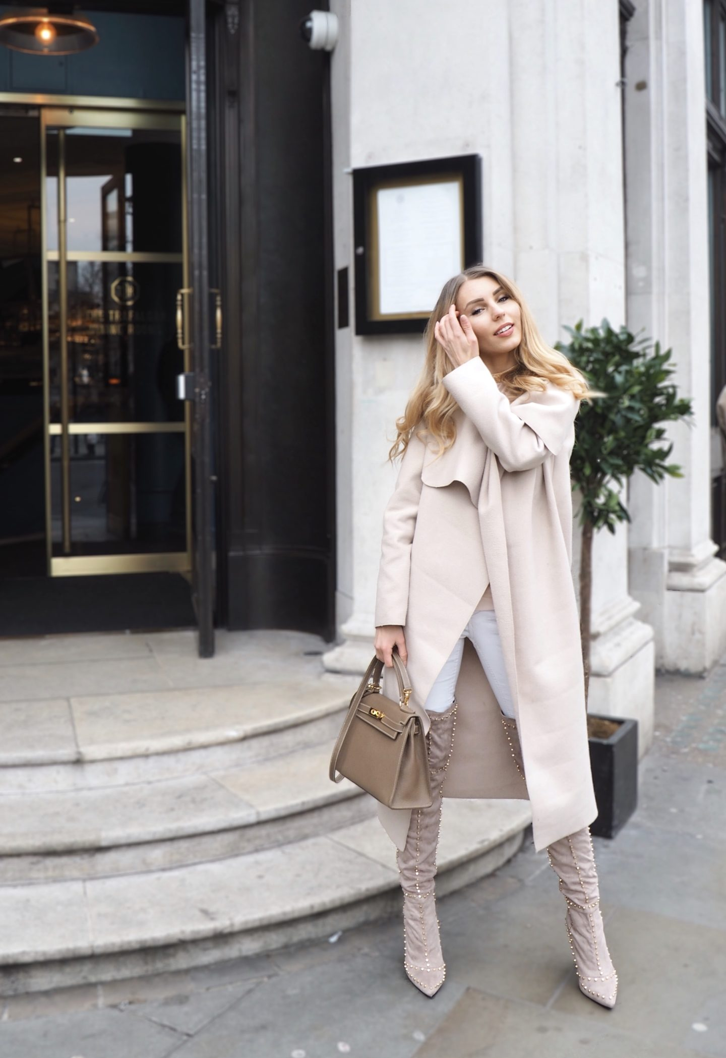 The Chic Pursuit is wearing an all nude outfit with a beige coat, beige Hermes Kelly inspired handbag, beige over the knee boots and a Sarah Ashcroft x In The Style nude mesh dress