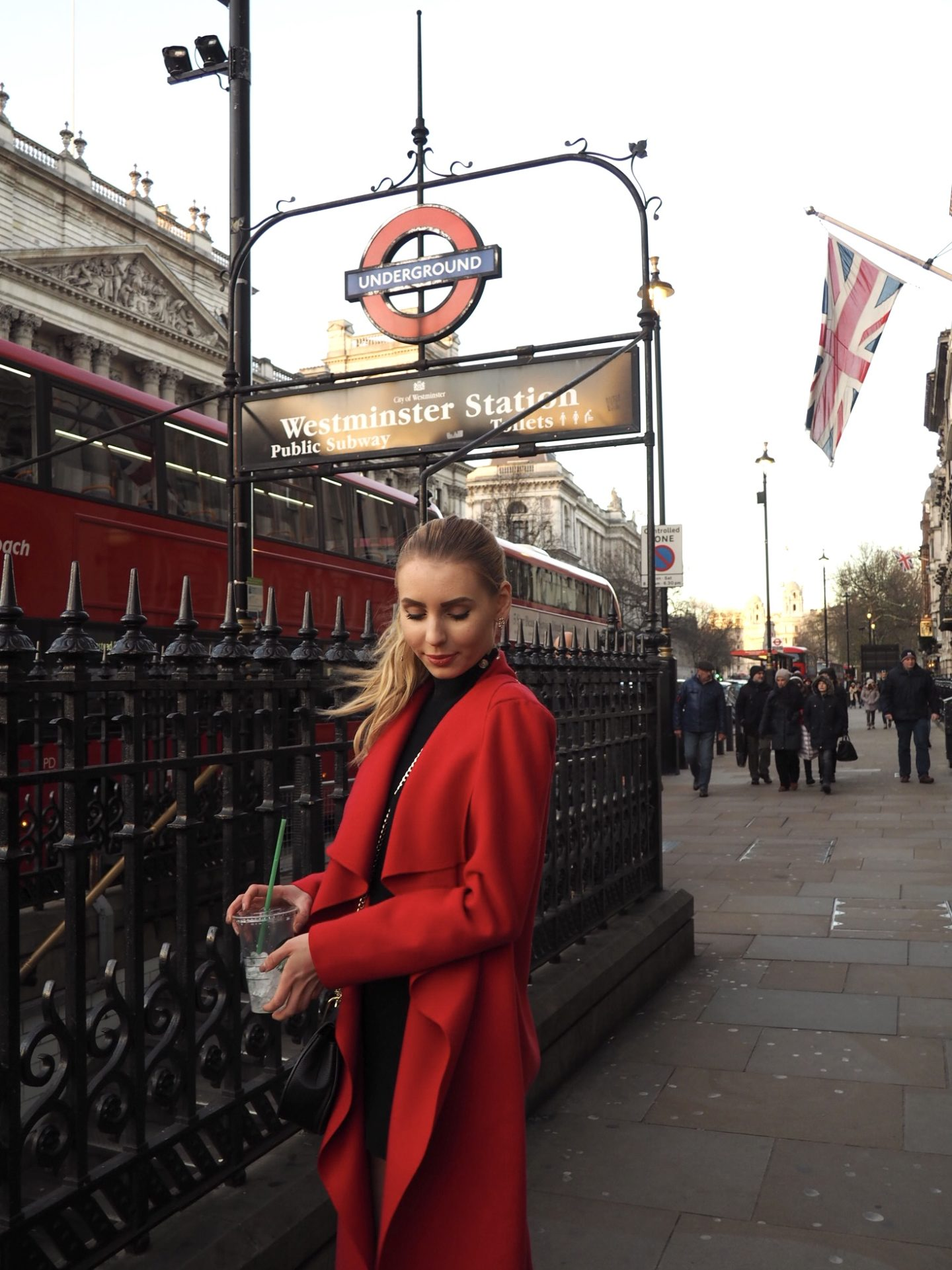 """The London fashion blogger """"Chic Pursuit """" is wearing a red waterfall coat with a black high neck dress with long sleeves, a black chain bag (Chloe drew dupe) and black over the knee boots in front of Westminster station."""