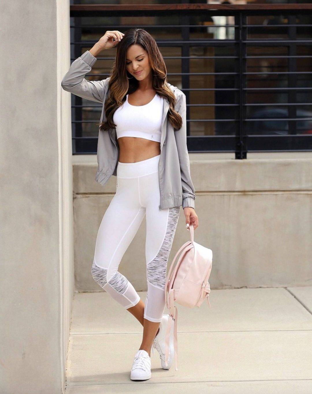 11+ Surprisingly Cute Sporty Outfits To Try: All athleisure lovers ahoy! Check out these sporty chic outfits, casual outfits and stylish gym outfits to get inspired for the new season. | White high waisted leggings with white sports bra, pink backpack and grey hoodie. Image ©MumuAndMacaroons #sportyoutfits #casualoutfits #athleisure