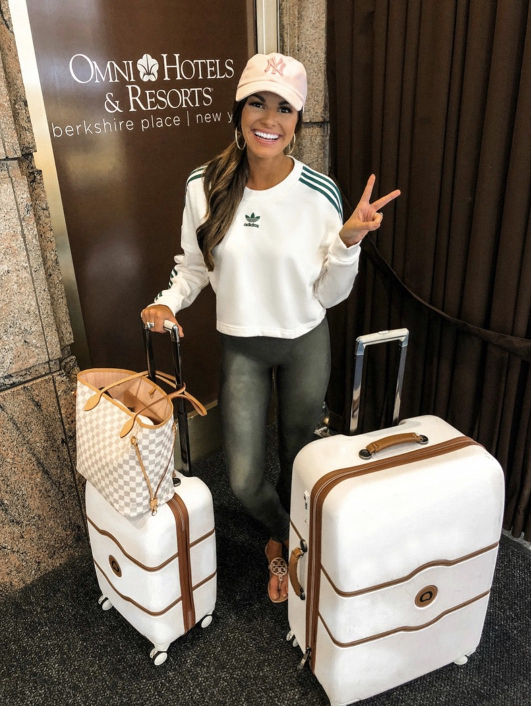 11+ Surprisingly Cute Sporty Outfits To Try: All athleisure lovers ahoy! Check out these sporty chic outfits, casual outfits and stylish gym outfits to get inspired for the new season. | Adidas shirt, pink Yankees cap, faux leather leggings, white luggage - perfect for airport outfits. ©MumuAndMacaroons #sportyoutfits #casualoutfits #athleisure #airportoutfits
