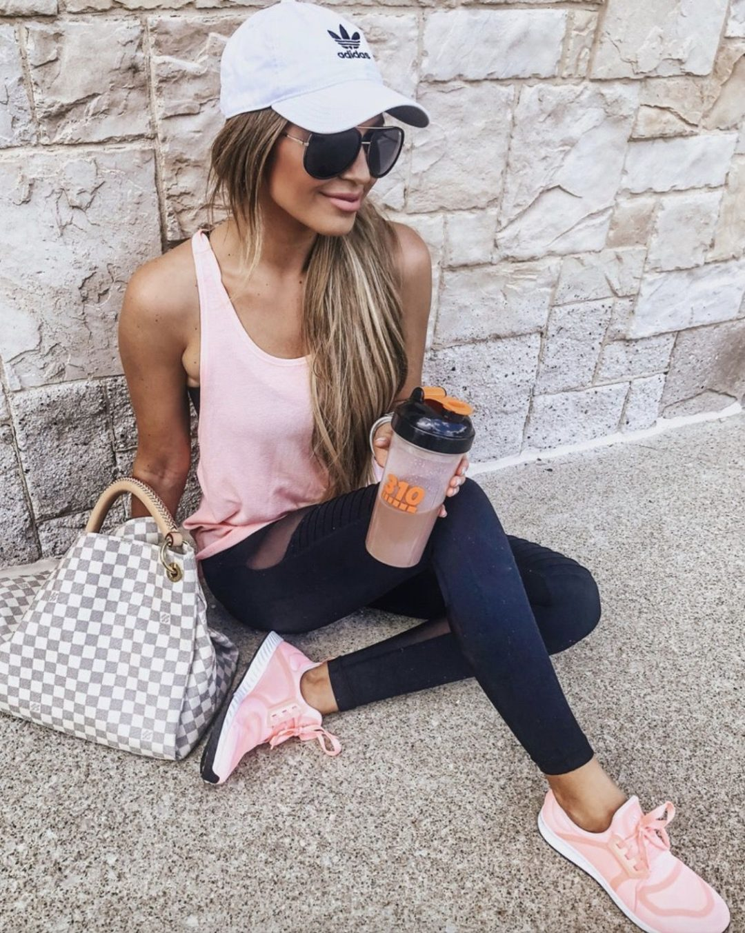 11+ Surprisingly Cute Sporty Outfits To Try: All athleisure lovers ahoy! Check out these sporty chic outfits, casual outfits and stylish gym outfits to get inspired for the new season. | White Adidas cap, pink sneakers, pink top, Louis Vuitton Neverfull - perfect for airport outfits. Image ©HollieWdwrd #sportyoutfits #casualoutfits #athleisure #airportoutfits